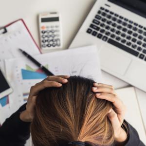 Eine Frau sitzt frustriert am Schreibtisch und hält sich den Kopf