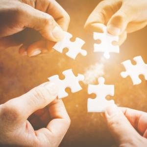 Mehrere Hände halten ein Puzzlestück und führen sie in der Mitte zusammen